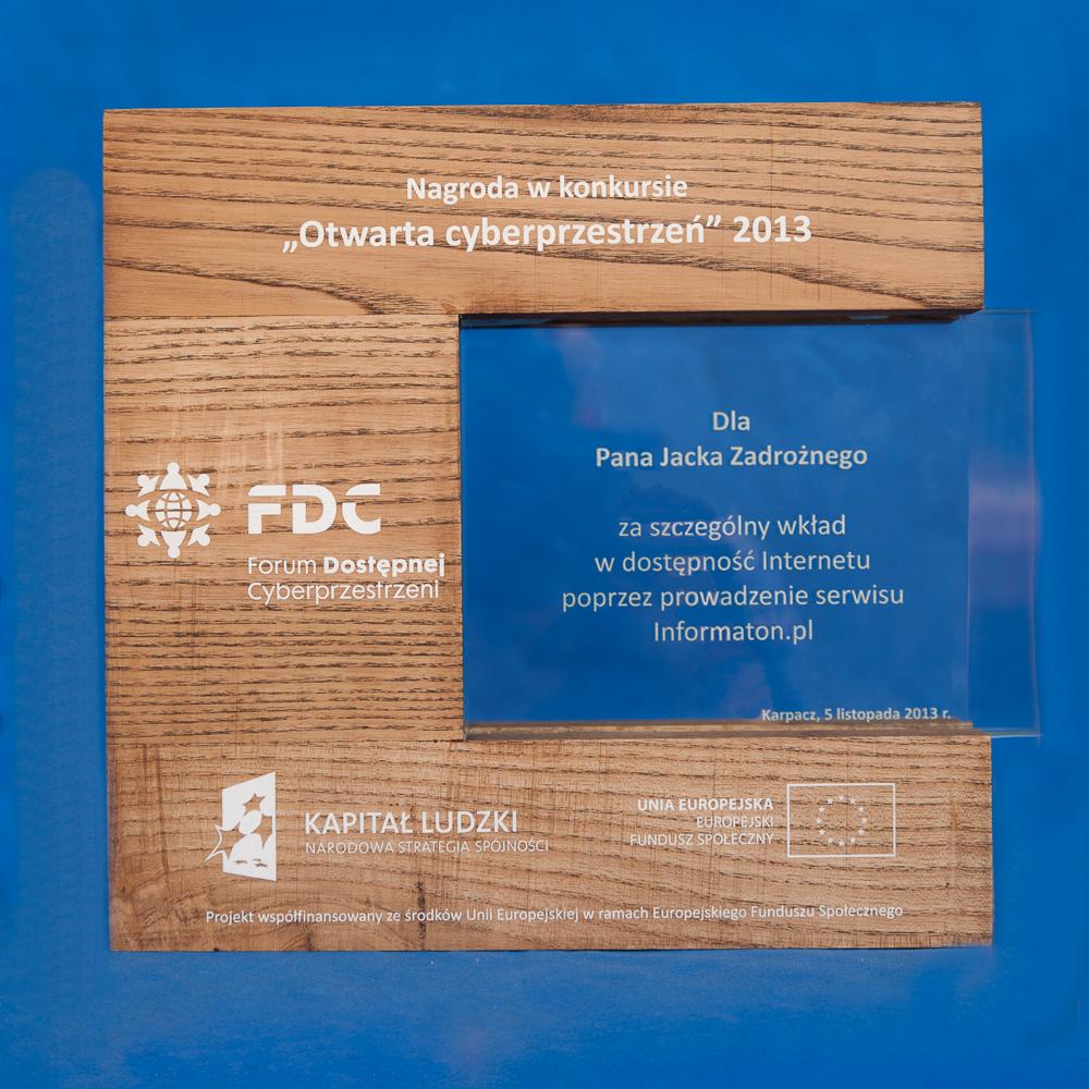 """Drewniana ramka, na której umieszczone są napisy w kolorze białym """"Nagroda w konkursie """"Otwarta cyberprzestrzeń"""" 2013"""" oraz logotypy Forum Dostępnej Cyberprzestrzeni, Kapitał Ludzki i Narodowa Strategia Spójności oraz Unia Europejska Europejski Fundusz Społeczny. Na szklanej płytce wmontowanej w drewnianą ramkę znajdują się napisy """"Dla Pana Jacka Zadrożnego za szczególny wkład w dostępność Internetu poprzez prowadzenie serwisu Informaton.pl. Karpacz, 5 listopada 2013 r."""""""